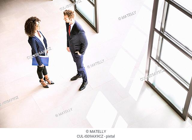 High angle view of businessman and woman talking at office entrance