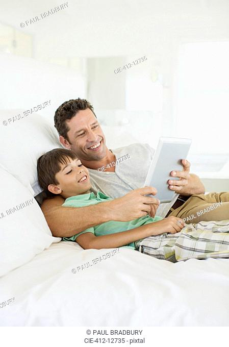 Father and son using digital tablet on bed