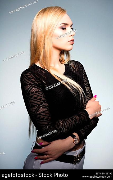 Glamor blonde posing in studio on a white background, wearing a black blouse and white pants
