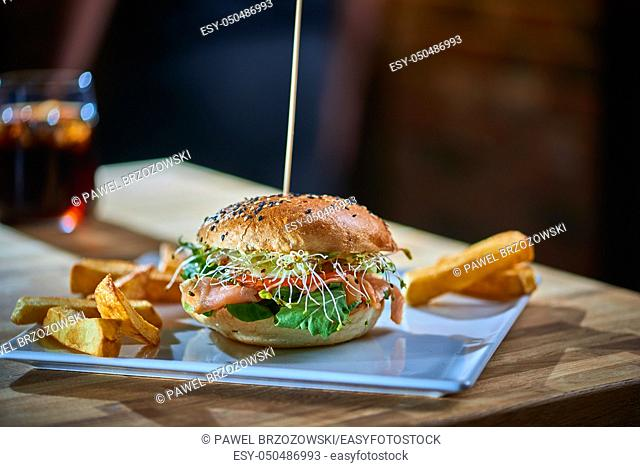 Salmon burger with wooden spike served with french fries. Blurred bar in the background. Copy space