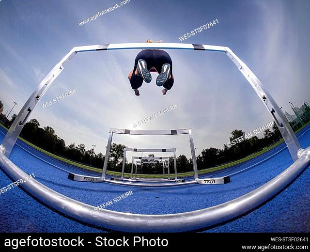 Athlete jumping over hurdle on track at training ground