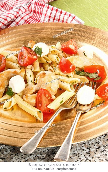 pasta salad with mozzarella, cherry tomatoes, basil and dry parsley
