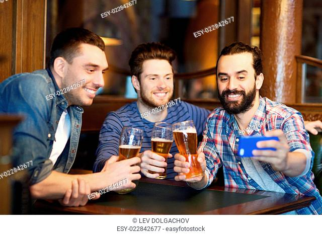 people, men, leisure, friendship and technology concept - happy male friends drinking beer and taking selfie with smartphone at bar or pub