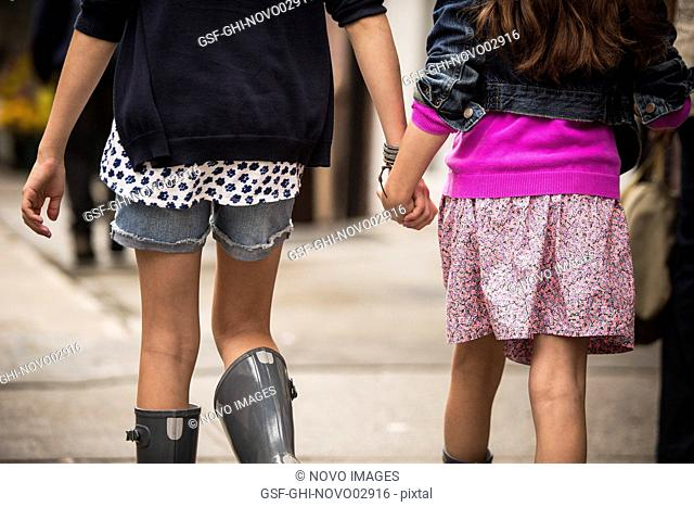Two Young Girls Holding Hands While Walking Down Sidewalk, Close-Up Rear View