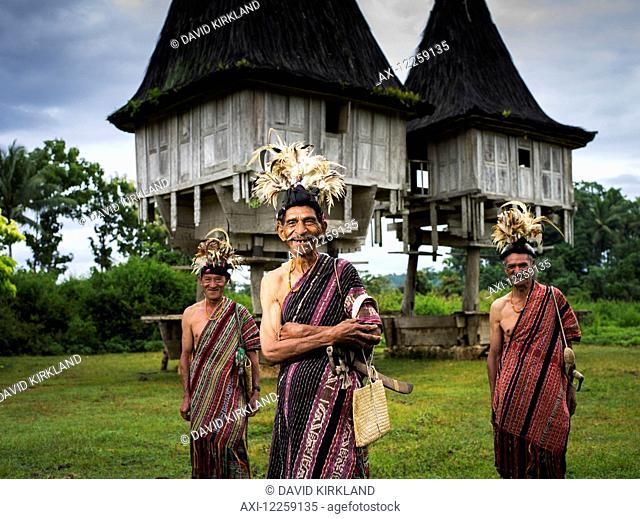 Elderly men in traditional attire standing in front of distinctive houses; Timor-Leste