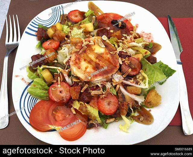 Mixed salad with strawberries, fruit jelly, tomato and coulis