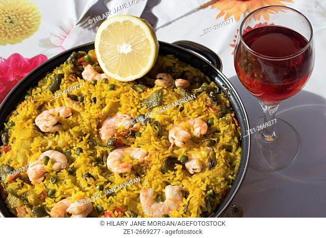 Spanish seafood paella and glass of red wine