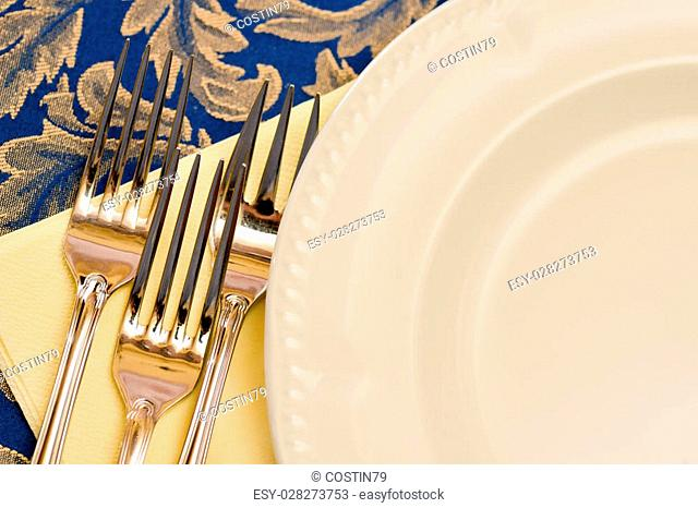 Three forks and white china plate on a table