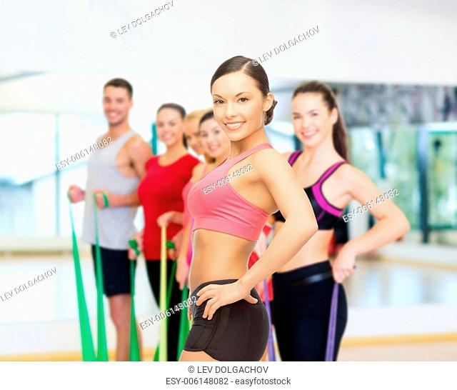 fitness, sport, training and lifestyle concept - personal trainer with group of smiling people in gym