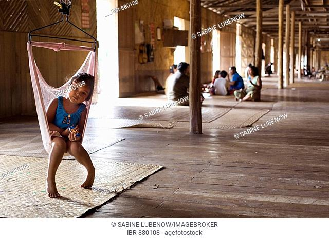 Girl on a swing in a traditional longhouse of the Iban, ethnic group, on Lemanak River, Sarawak, Borneo, Malaysia