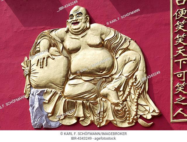 Laughing Buddha with stuffed alms-bag, golden relief, Ten Thousand Buddhas Monastery, Sha Tin, New Territories, Hong Kong, China