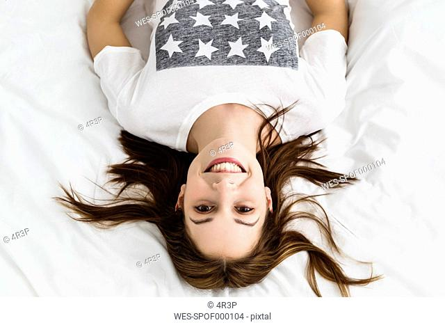 Portrait of young woman lying on bed, smiling