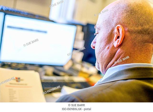 Over shoulder view of businessman reading paperwork at office desk