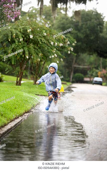 Boy in rubber boots running and splashing in rain puddle