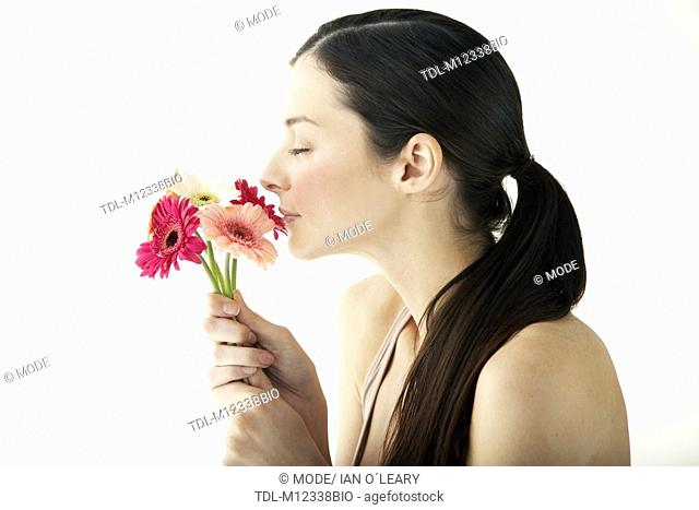A young woman smelling a bunch of flowers