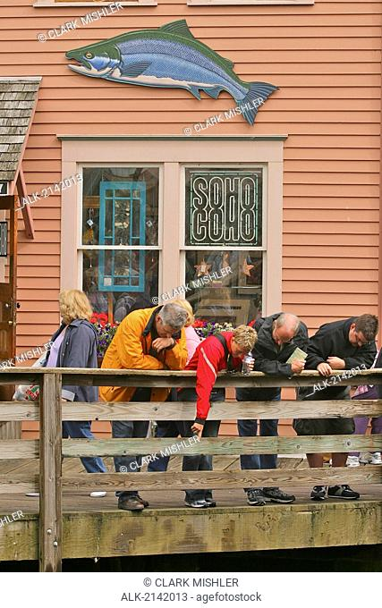 Tourists Look Over Railing Into The Waters Of Creek Street In Ketchikan, Alaska During Summer