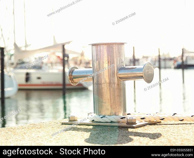 Stainless steel bollard with a rope in a luxury marina