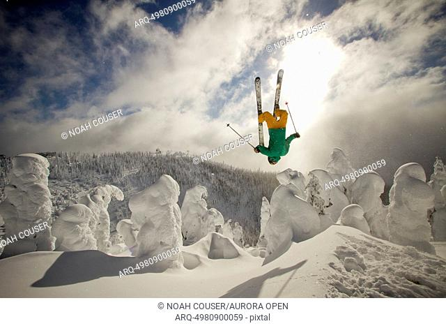 A skier throws a backflip off of a jump in the sunshine