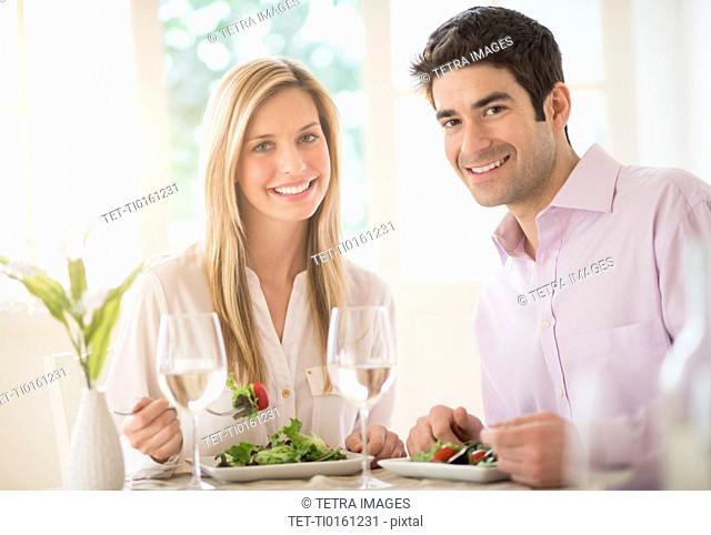Portrait of couple eating dinner in restaurant