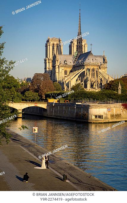 Wedding couple posing for early morning photos below Cathedral Notre Dame, Paris, France