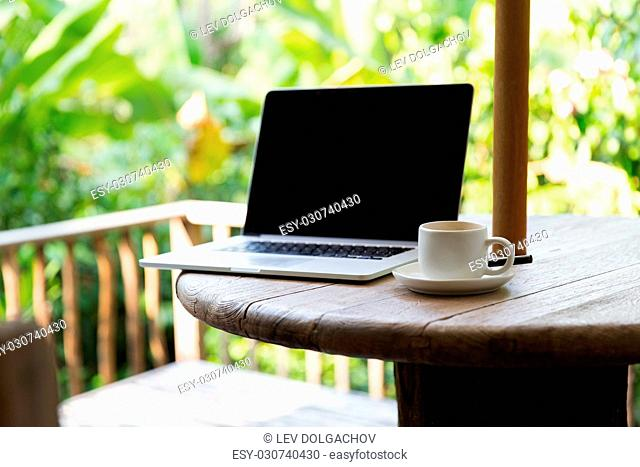 business, technology, drinks and objects concept - coffee cup and laptop computer on table outdoors