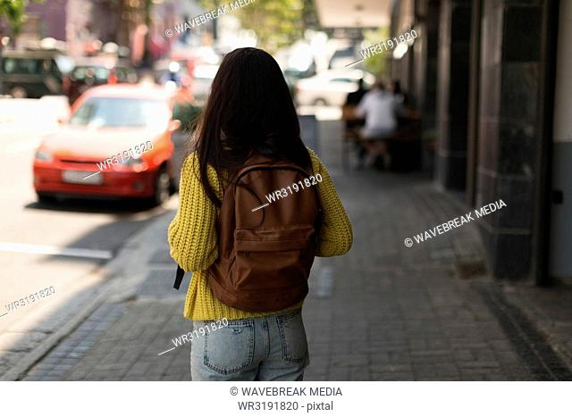 Teenage girl standing with backpack in the city