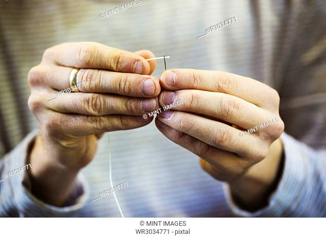 A craftsman's hands holding a leatherwork needle and threading cord through the eye of the needle