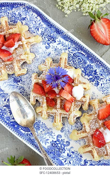 Strawberry and elderberry waffles on a blue plate with cornflowers and elderflowers