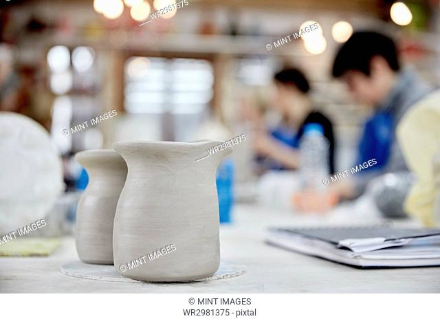 Two clay jugs in the foreground. A ceramics class taking place, people seated at a workbench in a pottery studio