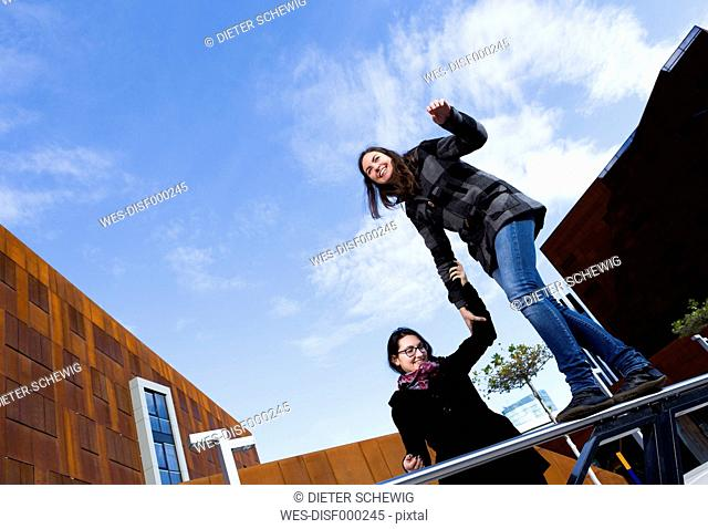 Young woman balancing and being assisted by friend