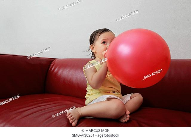 Young girl blowing up red balloon