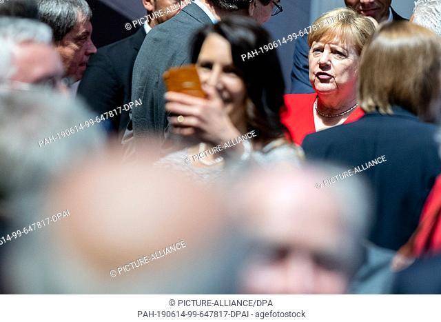 14 June 2019, North Rhine-Westphalia, Bonn: German Chancellor Angela Merkel (CDU, r, in red) is standing on stage after her 25th anniversary speech at the Haus...