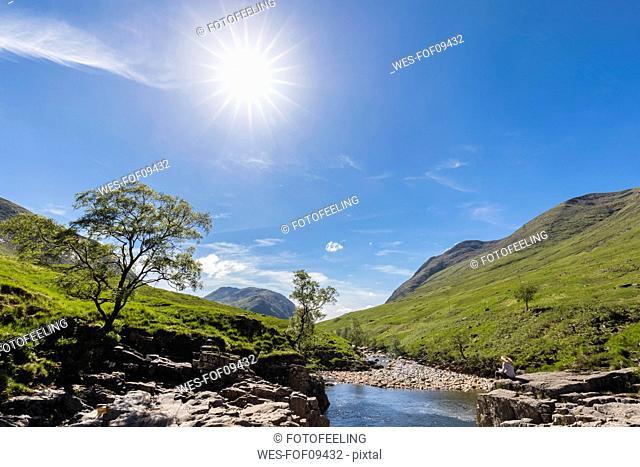 Great Britain, Scotland, Scottish Highlands, Etive with River Etive, female tourist reading