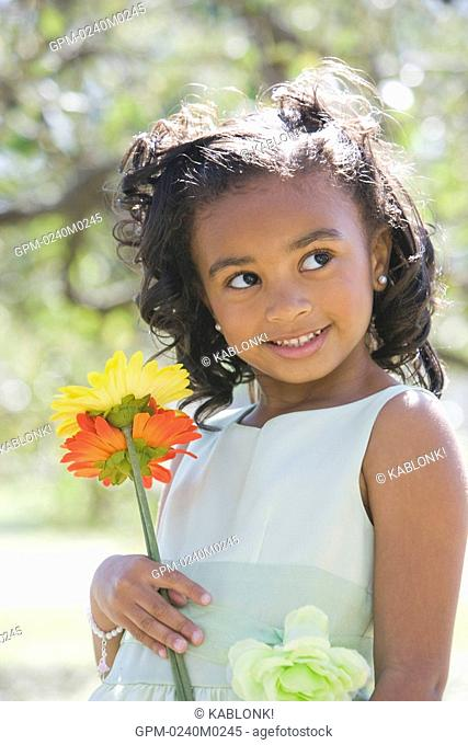 Portrait of African American girl in dress standing in park holding flowers