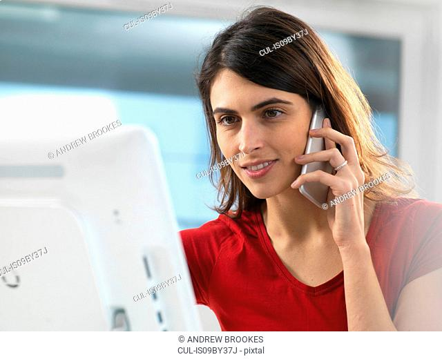 Woman working at computer and using mobile phone in office