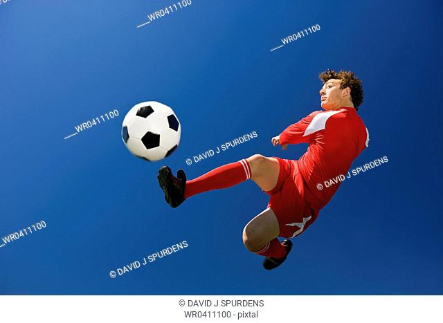 A soccer player volleys a ball in mid air