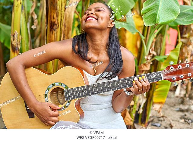 Happy woman playing guitar outdoors