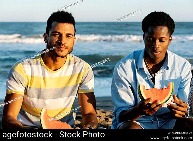 Young friends eating watermelon while sitting on beach