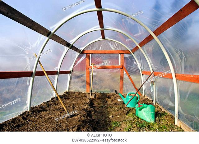 early spring time greenhouse inside construction with gardener tools and earth soil