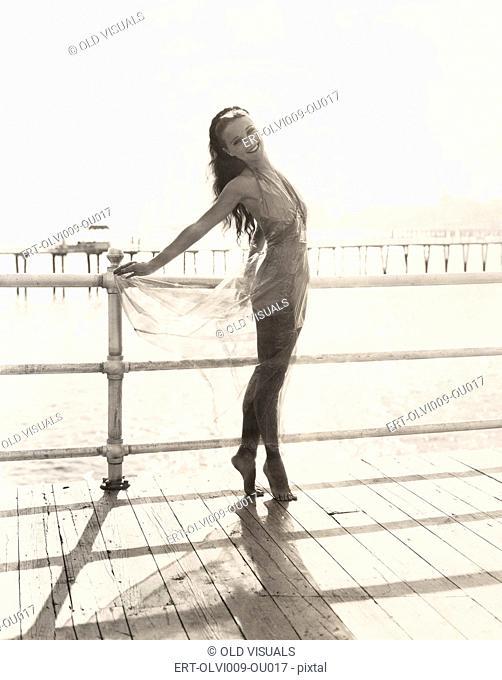 Woman in bathing suit on tiptoes posing on pier