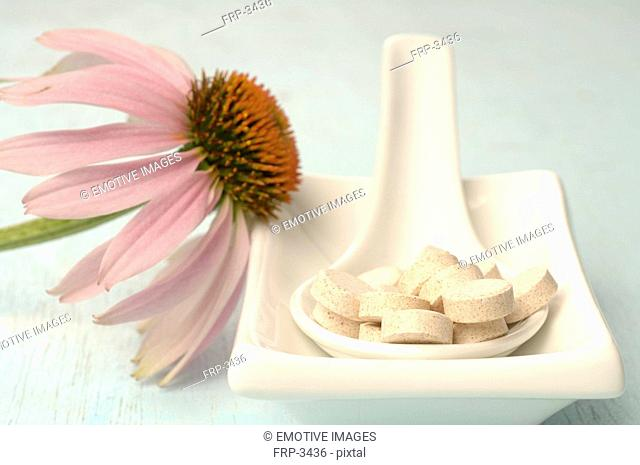 Echinacea blossom in a small bowl with pills in a spoon