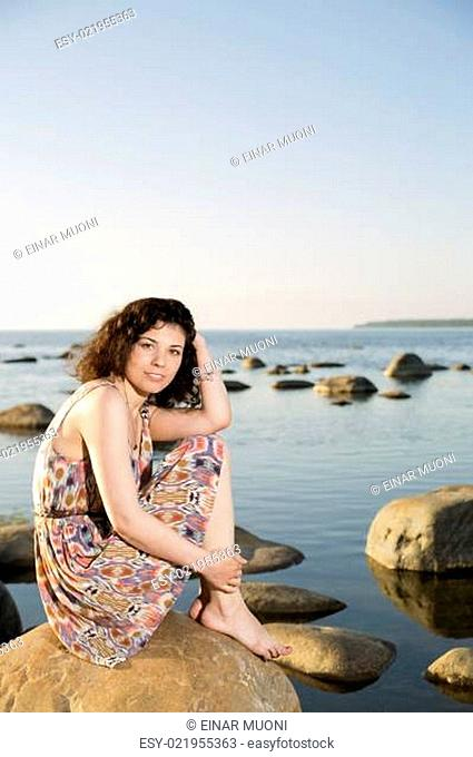 Woman barefoot sitting at stone at evening