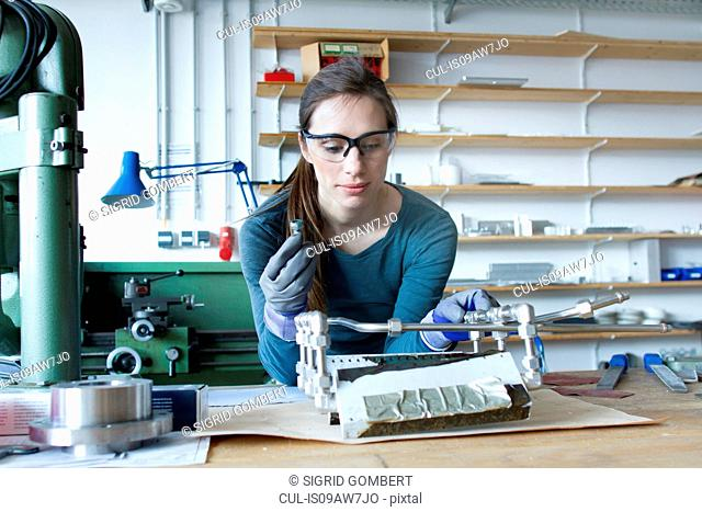 Woman wearing latex gloves and safety goggles building model