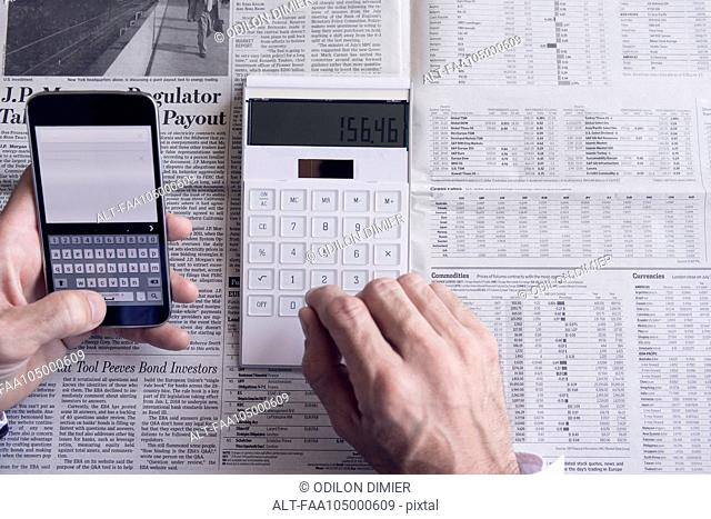Investor using smartphone and calculator