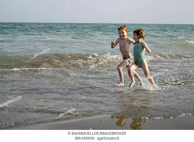 Mr two children are running at the beach