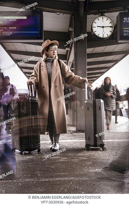Fashion blogger Esra Eren aka @nachgestern waiting with trolley bags at Munich central station, Germany