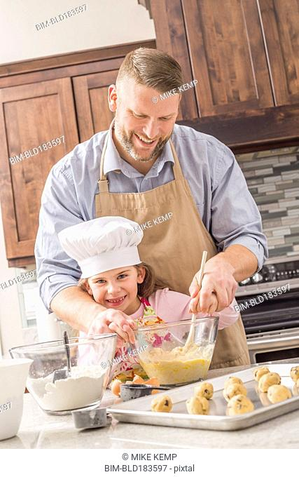 Caucasian father and daughter baking in kitchen