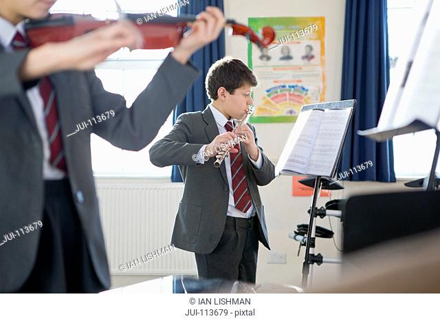 High school students playing flute and violin in music class