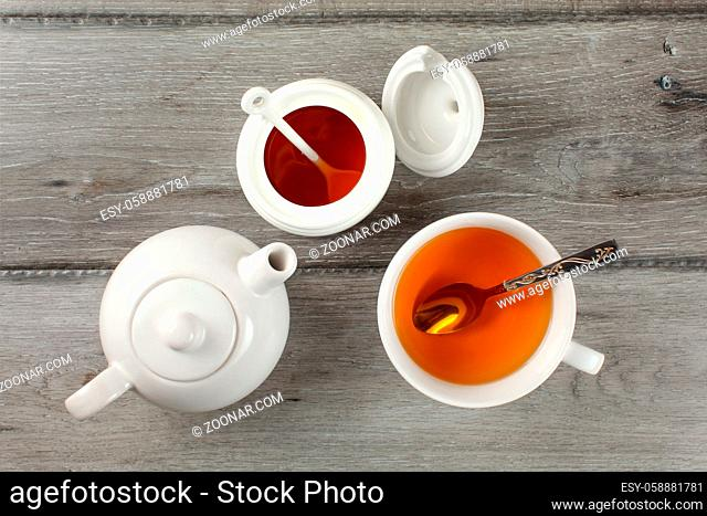 Table top view - gray wood desk with teapot, teacup with hot drink, silver spoon and small white porcelain honeypot