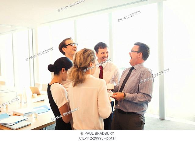 Laughing business people enjoying coffee break in conference room